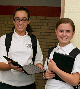 Two female students pose in the hallway